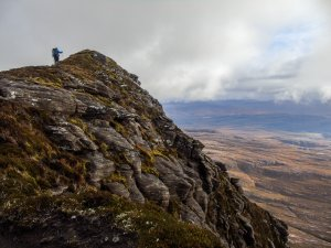 Climber at peak of mountain