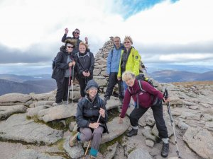 Hiking group poses at the top of one of Scotland's mountain peaks.