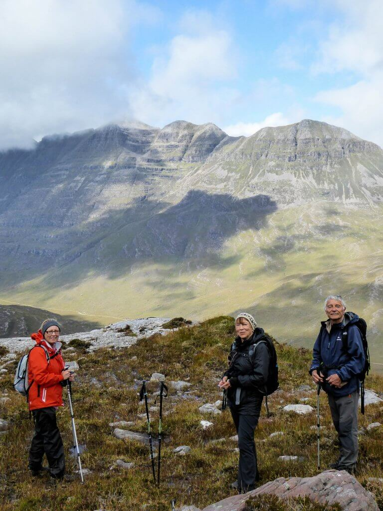 Three hikers admire Scotland's mountains